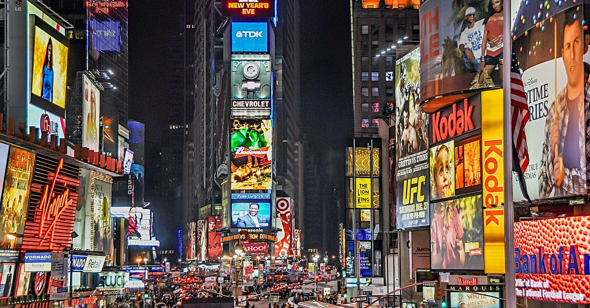 A close up of a busy city street with Times Square in the background
