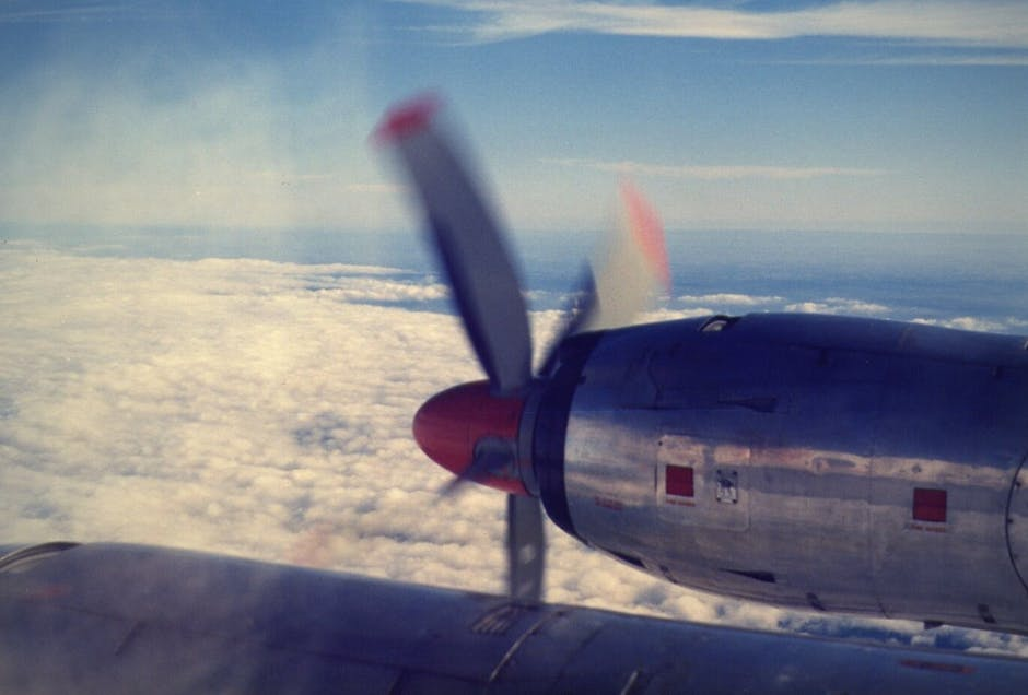 A close up of a propeller plane that is flying in the air